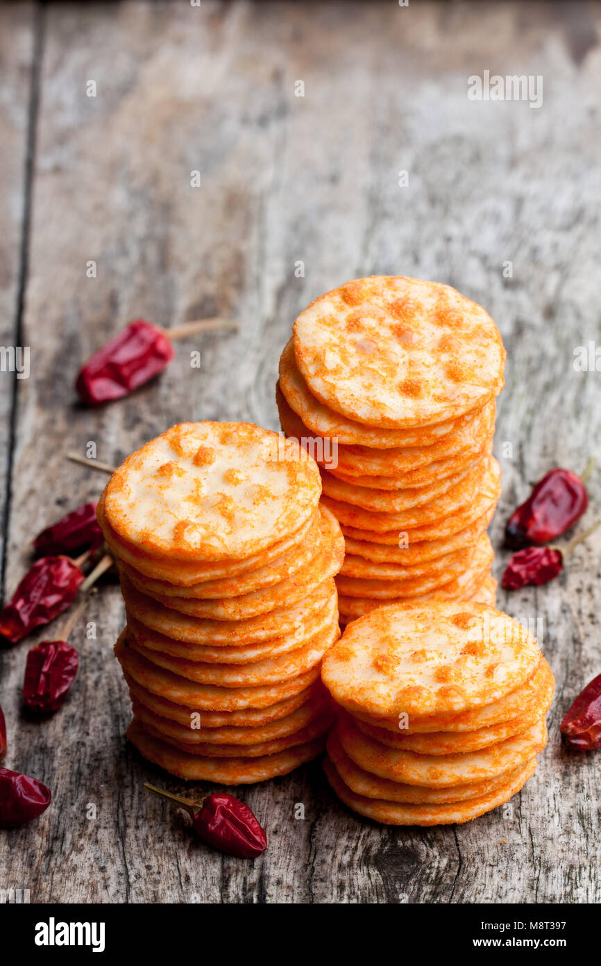 Round  shape rice cracker with chili pepper on wooden table - Stock Image