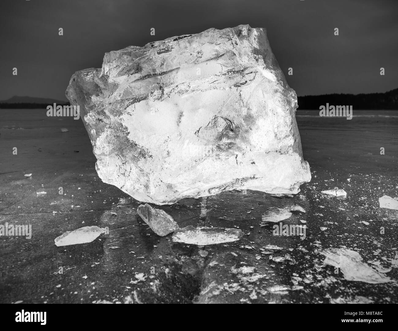 Blocks of shining ice and snow on the shore. The floes and crushed ice  during the evening and dark  hours when - Stock Image