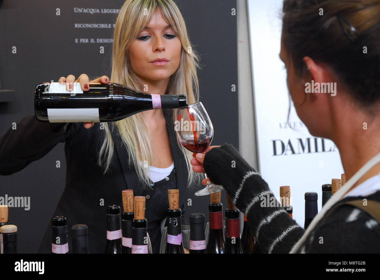 Blonde woman pouring red wine from the bottle to the glass of customer Stock Photo