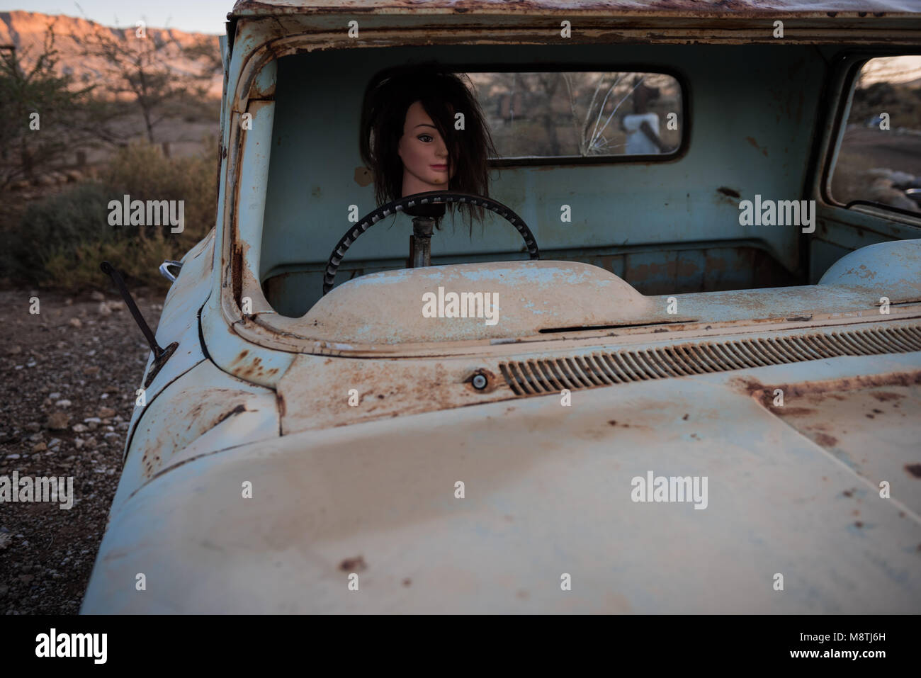 A mannequin head set in a car as part of the sculpture garden at Namibia's Tsauchab river camp - Stock Image