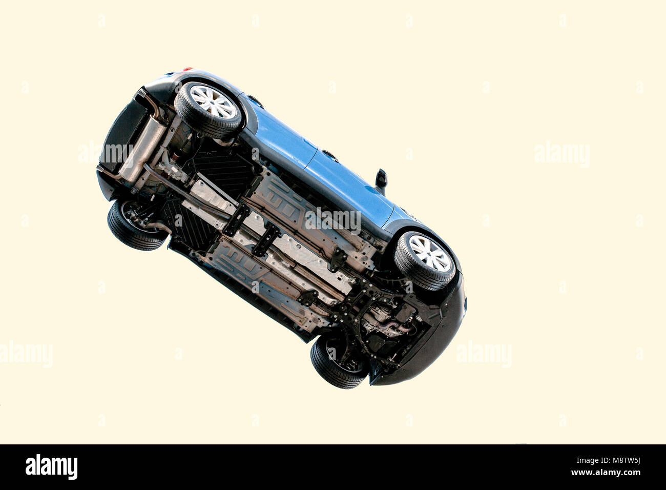 A car flying through the air (in the pale blue sky) with the underside including, wheels, engine and exhaust pipe - Stock Image