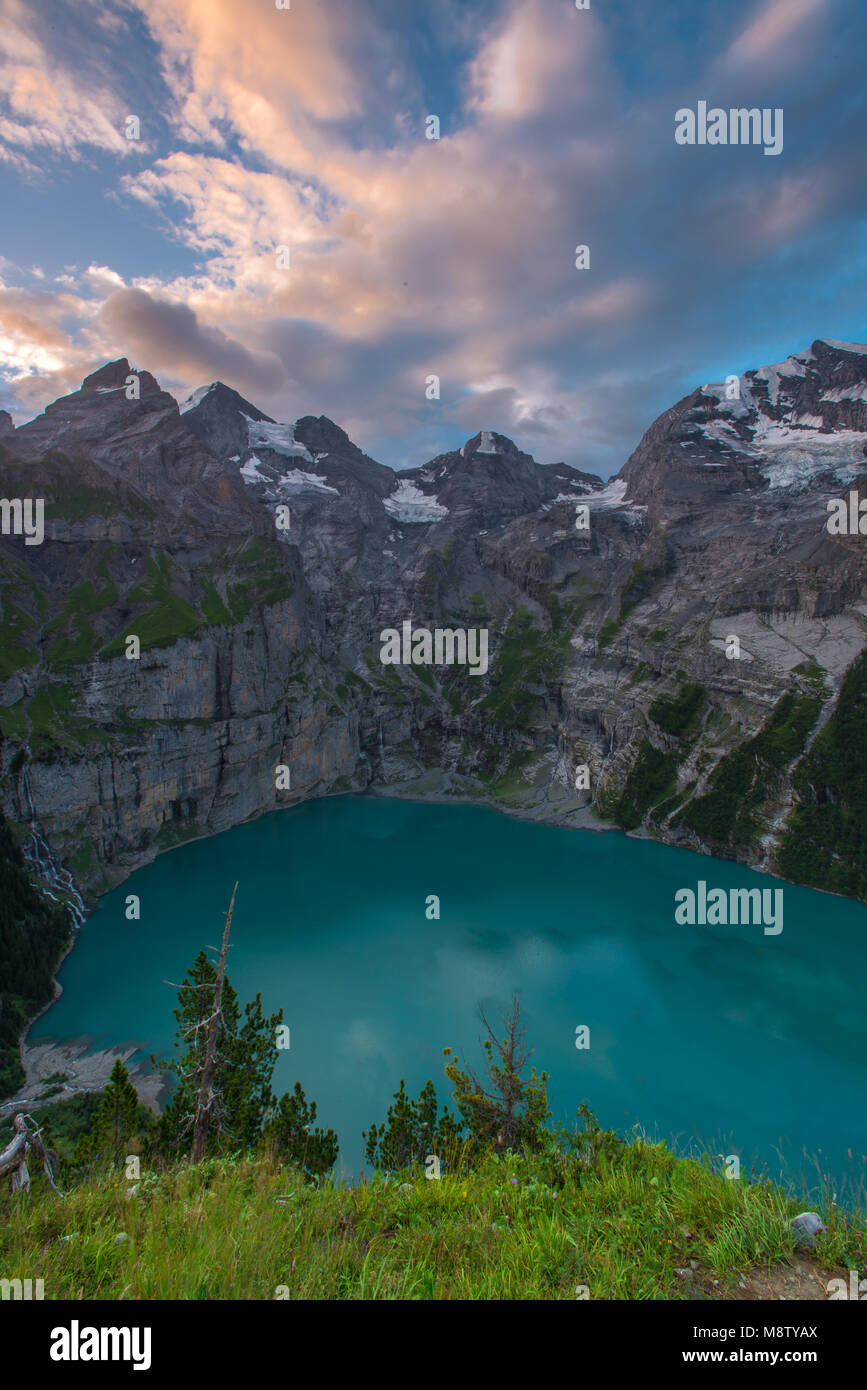Wonderful Oeschinen lake at sunrise, cirque of mountains surrounding the alpine tarn. Colorful, painted sky and - Stock Image