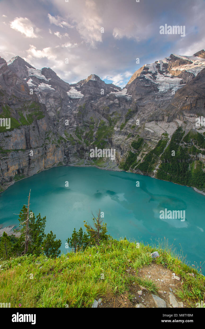 Spectacular view from a high ledge, cliff of an alpine lake at sunrise. Colorful sky, forest and mountains frame - Stock Image