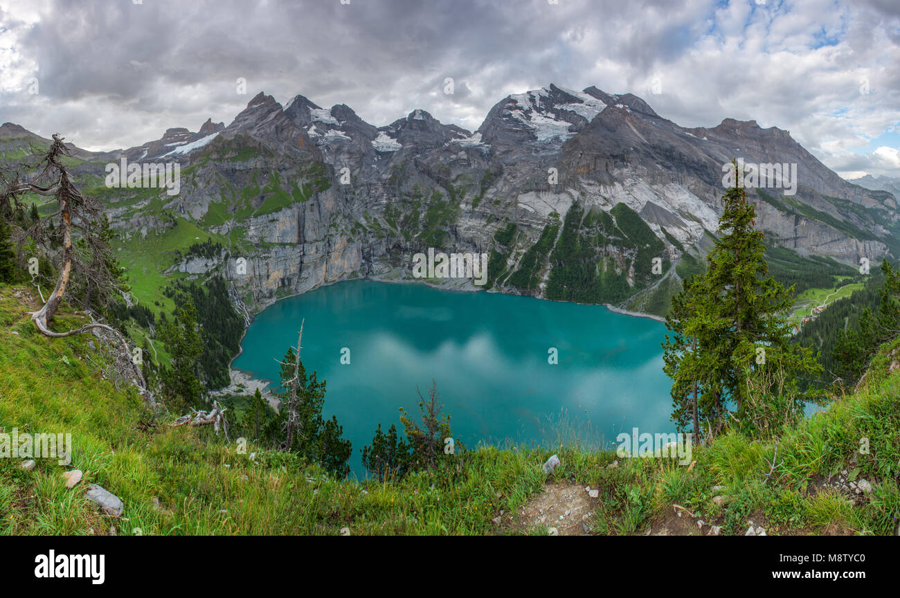 Great panoramic view from an overhang of Oeschinen lake, glacial lake in the Swiss Alps. Mountain cirque, range, - Stock Image