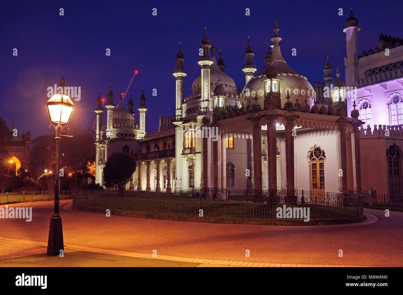 Brighton Pavilion illuminated at dusk from inside the grounds of the Royal Pavilion Garden, East Sussex, England, - Stock Image