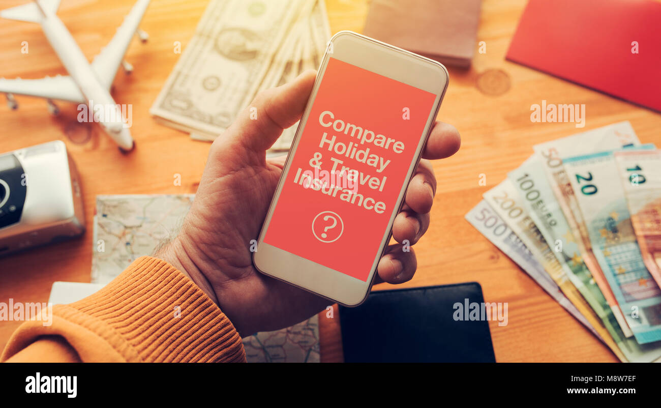 Compare holiday and travel insurance. Man holding smartphone with mock up app screen related to holiday vacation - Stock Image