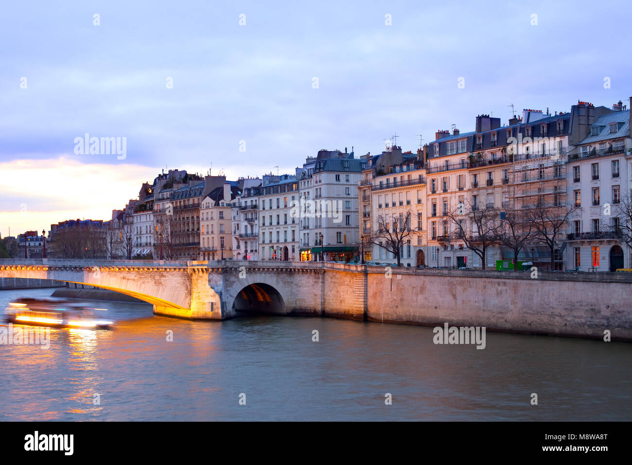 Boat on the Seine River passing by Pont de la Tournelle bridge in front of Ile Saint Louis, Paris, France - Stock Image