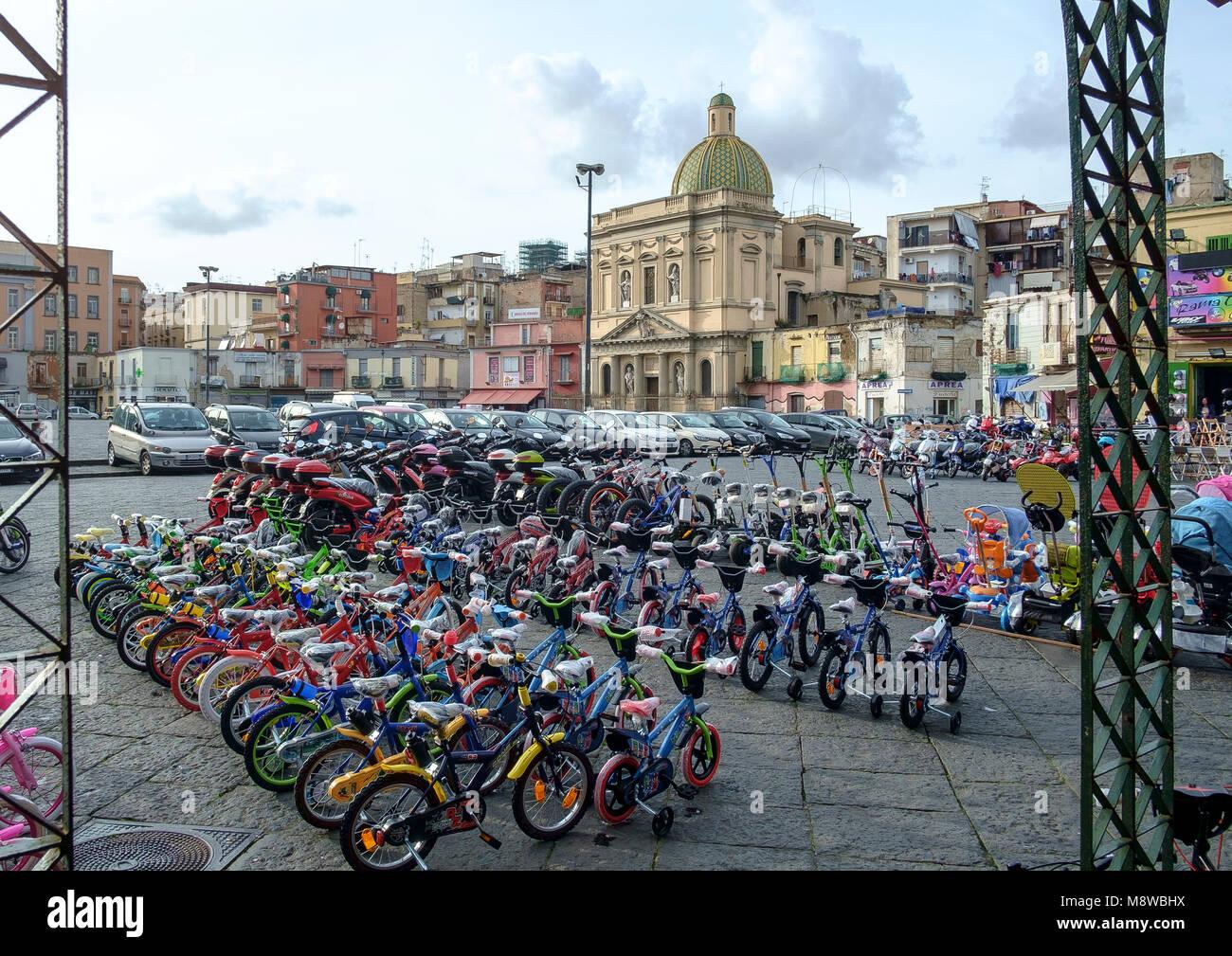 Childrens' bikes for sale on Piazza Mercato in Naples with the church of Santa Croce e Purgatorio al Mercato - Stock Image