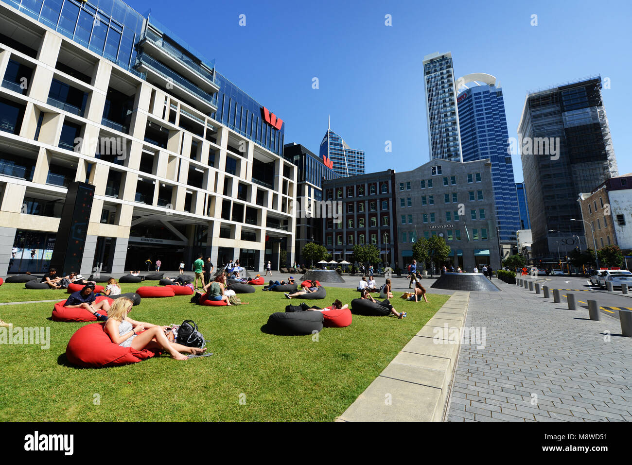 Locals relaxing on the Takutai Lawn at the Talitao square in Auckland's city center. - Stock Image
