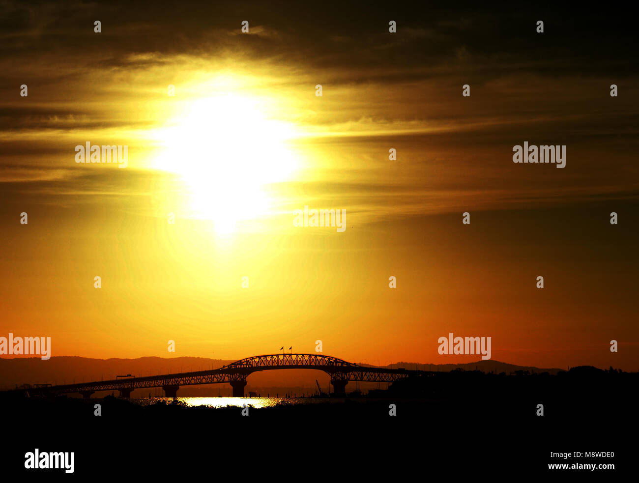 Sunset over the Auckland Harbour Bridge. - Stock Image