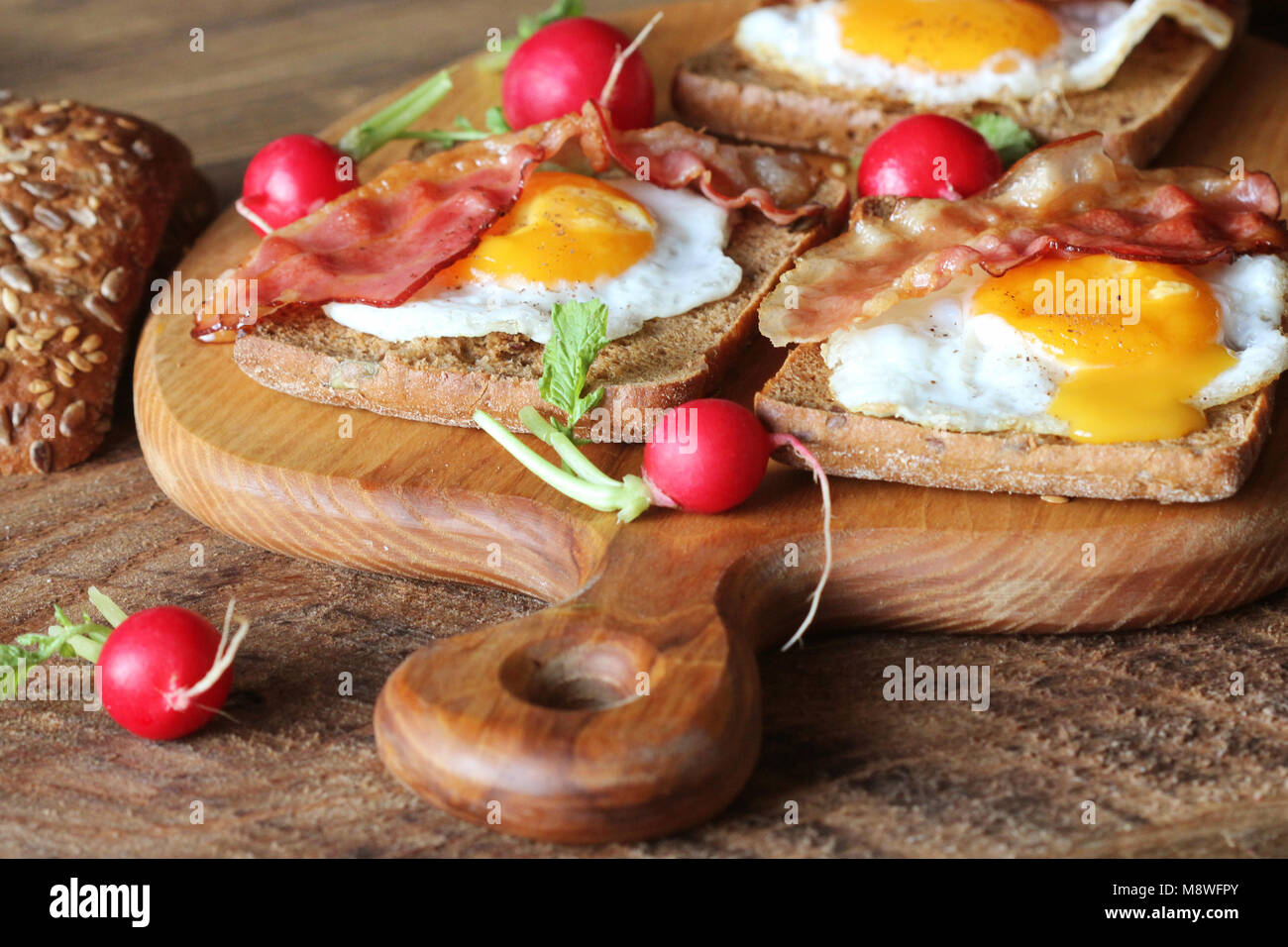 Breakfast of crispy bacon, fried eggs and bread. Sandwiches on cutting board. Rustic table . - Stock Image