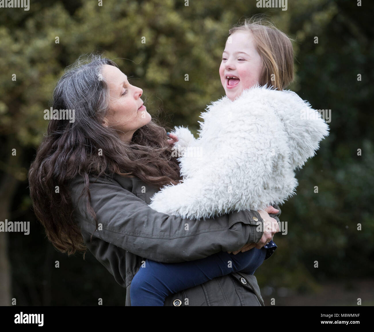 Ailith Harley-Roberts with her daughter Thalia, eight, who has Down syndrome, in Chapel Allerton Park in Leeds ahead - Stock Image