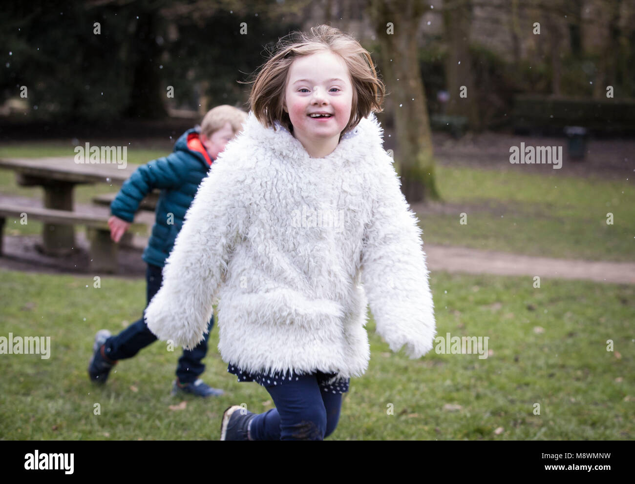 Thalia Harley-Roberts, eight, who has Down syndrome plays in Chapel Allerton Park in Leeds ahead of World Down Syndrome - Stock Image
