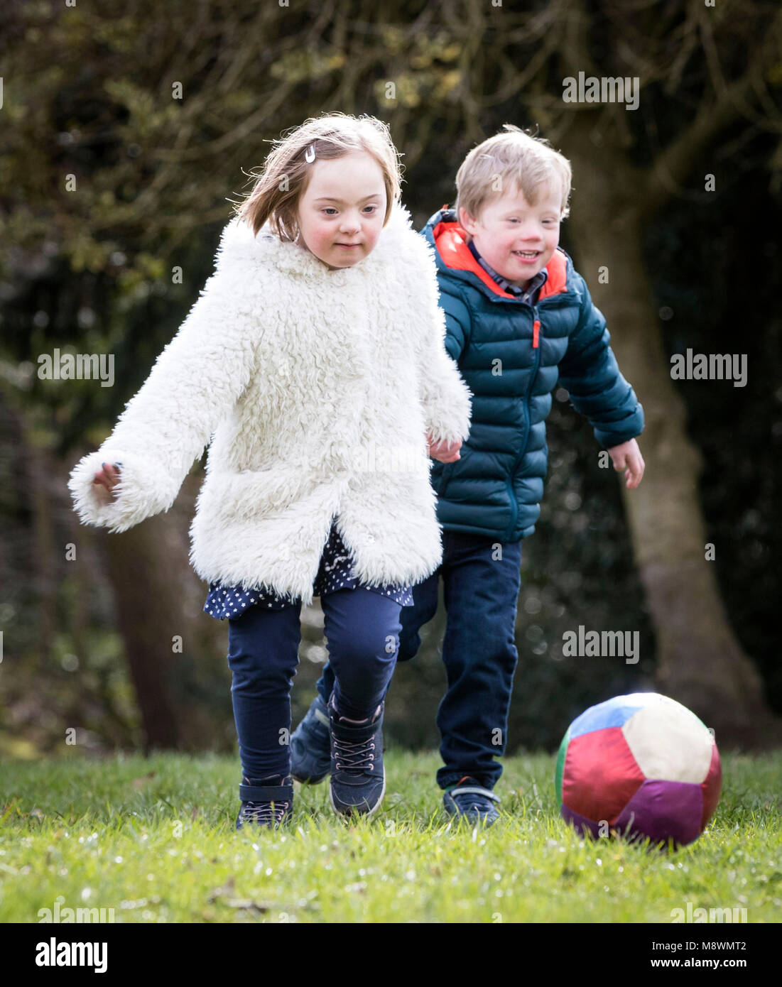 Thalia Harley-Roberts, eight, and Alby Davies, four, who both have Down syndrome play in Chapel Allerton Park in - Stock Image