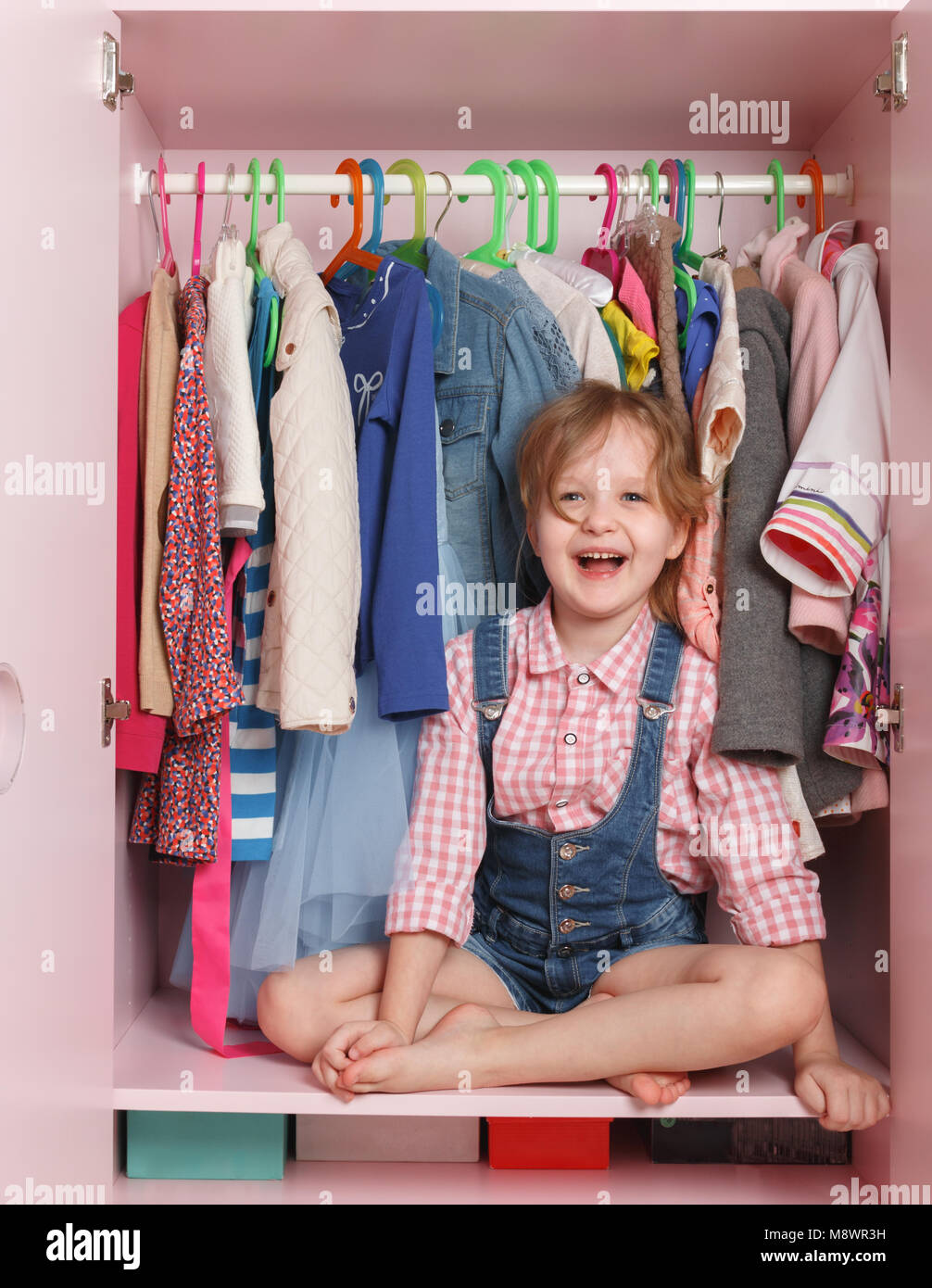 A little girl is sitting in a closet with a children's department. Storage system for children's things Stock Photo