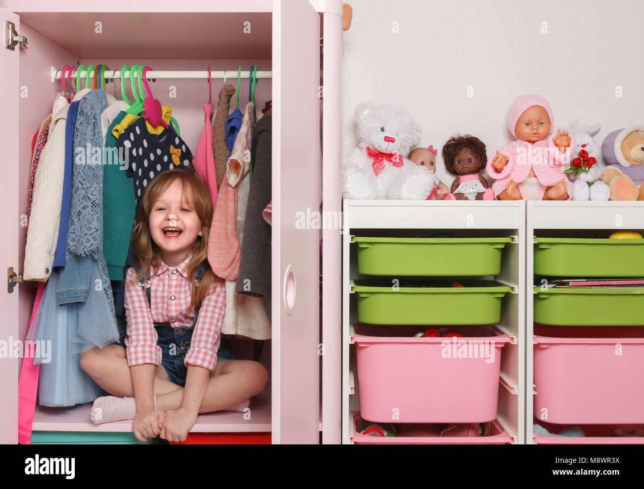 A little girl is sitting in a closet with a children's departmen - Stock Image