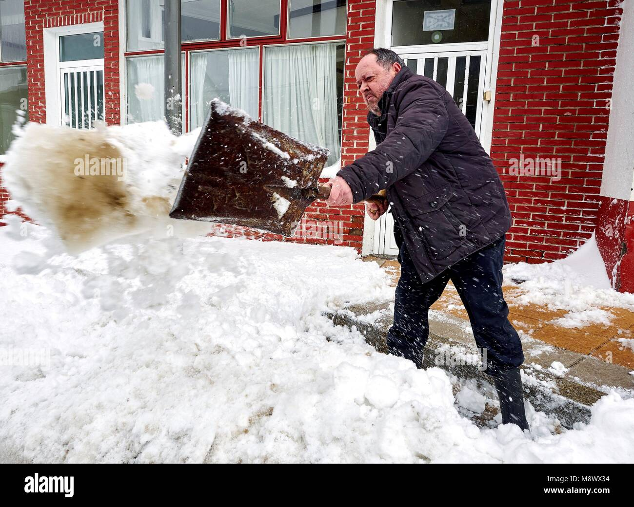 A man clears the snow in O Cebreiro, Lugo, Spain, 20 March 2018. A cold front has arrived to the peninsula lowering Stock Photo