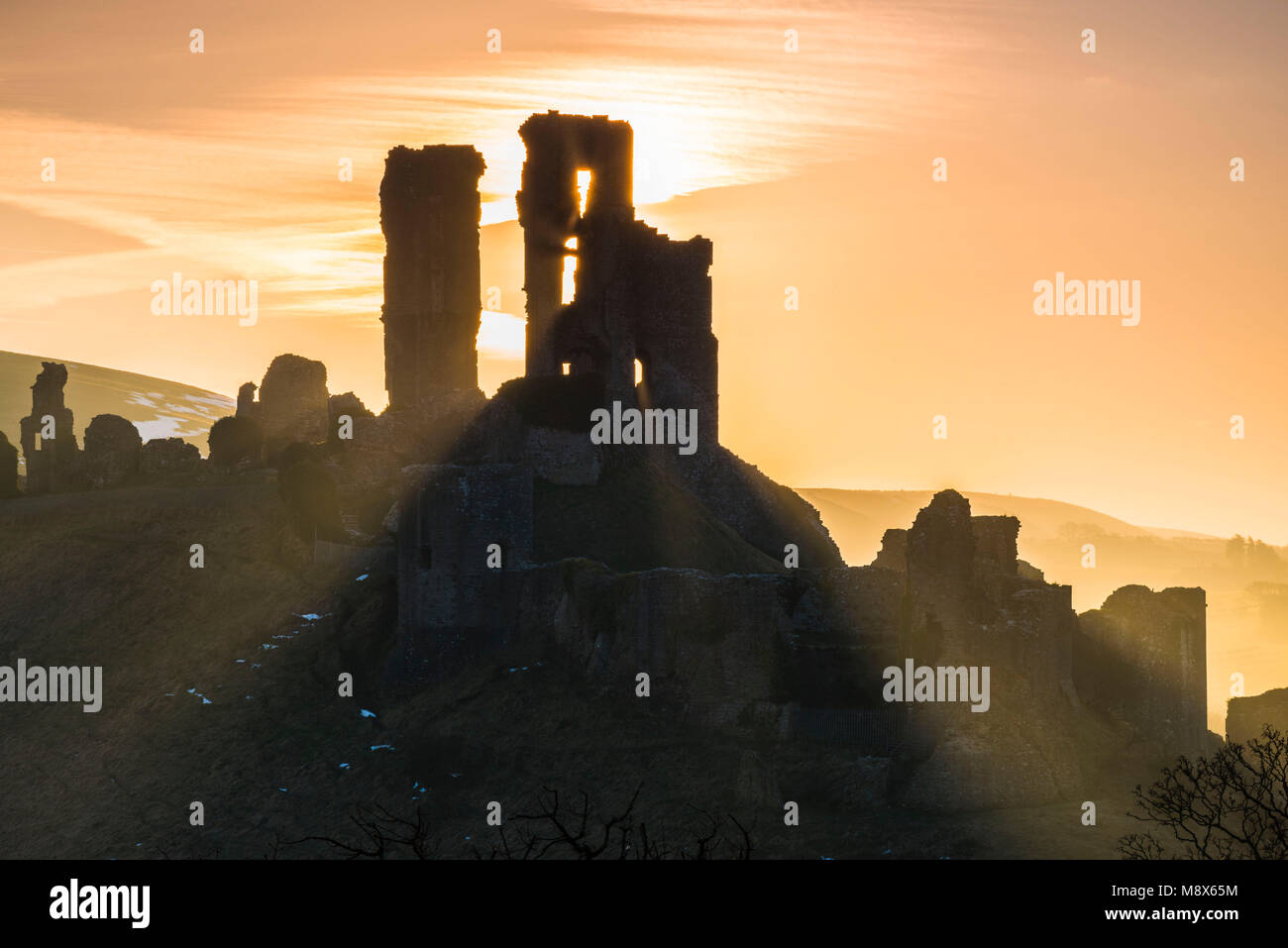Corfe Castle, Dorset, UK.  21st March 2018.  UK Weather. Beams of sunlight shine through and around the silhouette Stock Photo
