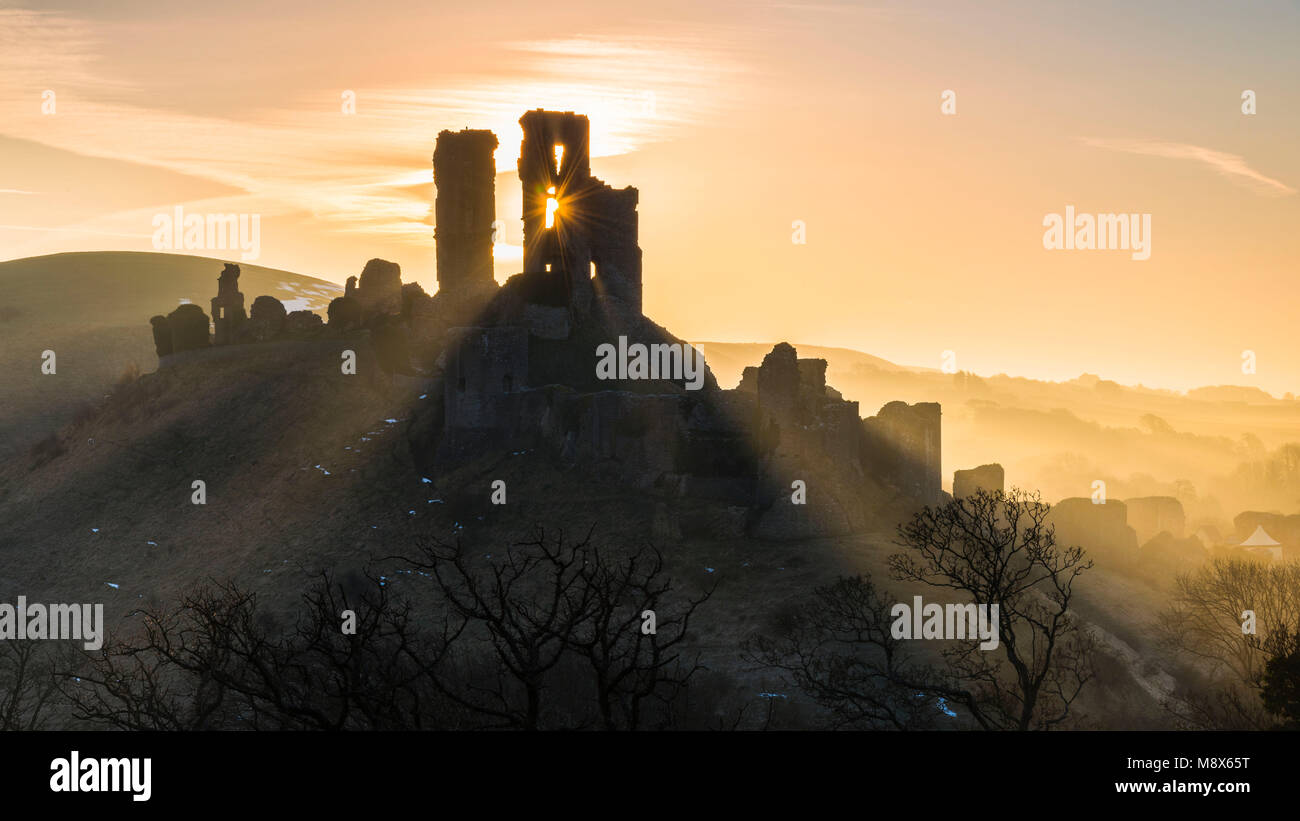 Corfe Castle, Dorset, UK.  21st March 2018.  UK Weather. Beams of sunlight shine through and around the silhouette - Stock Image