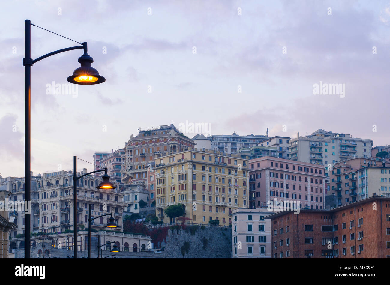Street lamps lighting up as the evening sets in the residential district of Genoa, San Teodoro, with the architectural - Stock Image