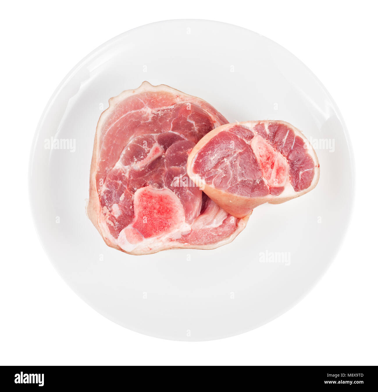 Raw pork knuckle on plate isolated on white background. Top view. - Stock Image