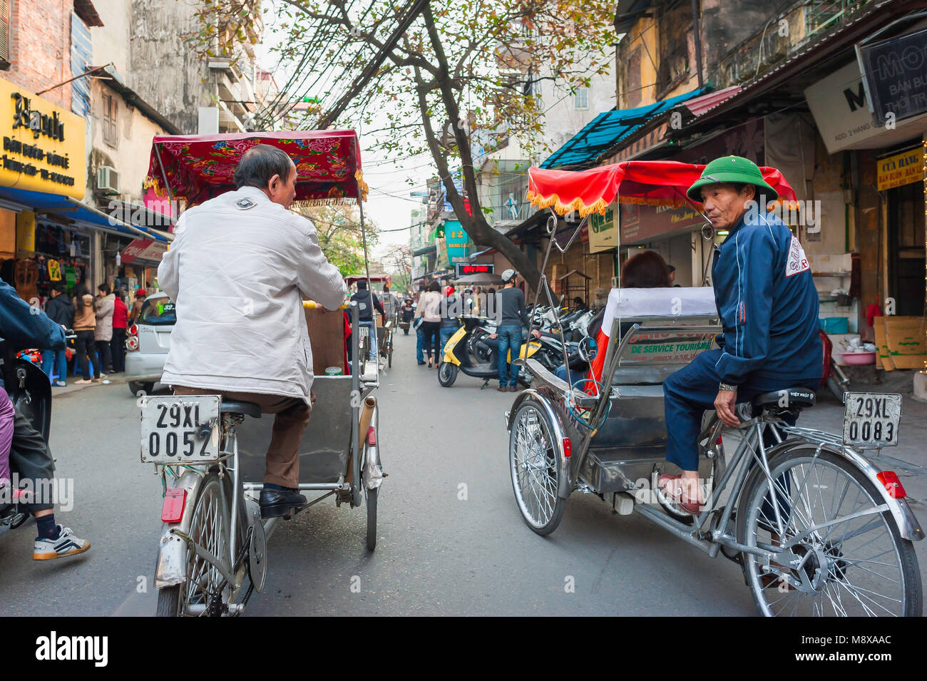 Vietnam rickshaw, two rickshaw drivers chat while taking their passengers on a tour of the Old Quarter in the center Stock Photo