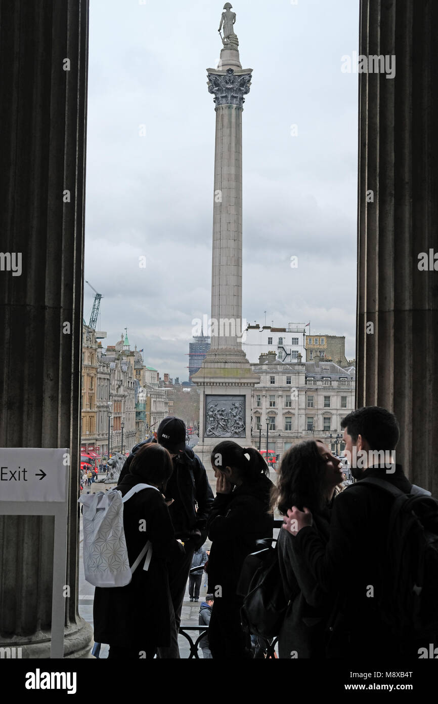 Tourists kiss with Nelsons column in the background. - Stock Image