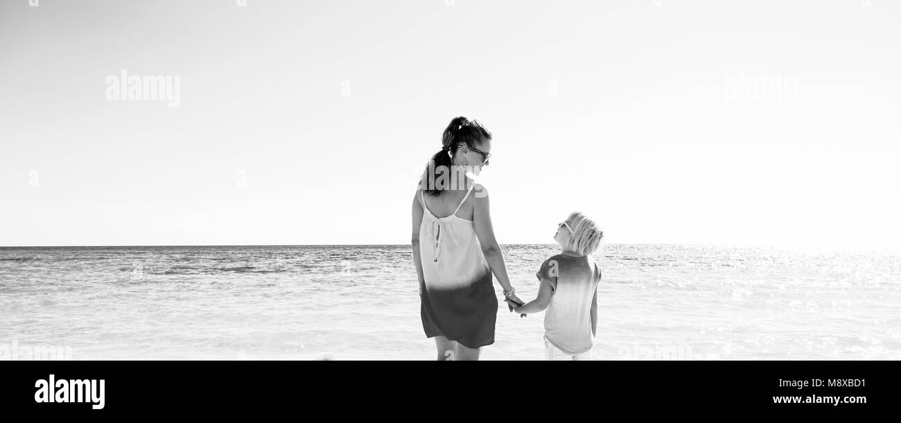 Colorful and wonderfully cheerful mood. happy trendy mother and daughter in colorful clothes on the beach looking - Stock Image