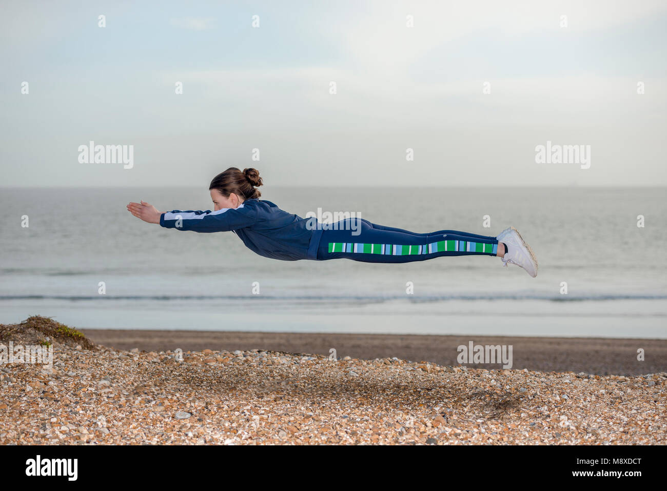 woman wearing a blue tracksuit outstretched in a dive pose levitating above the ground - Stock Image