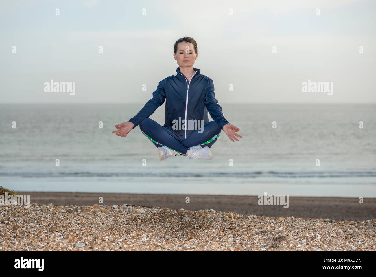 woman wearing a blue tracksuit in the lotus yoga position levitating above a beach - Stock Image