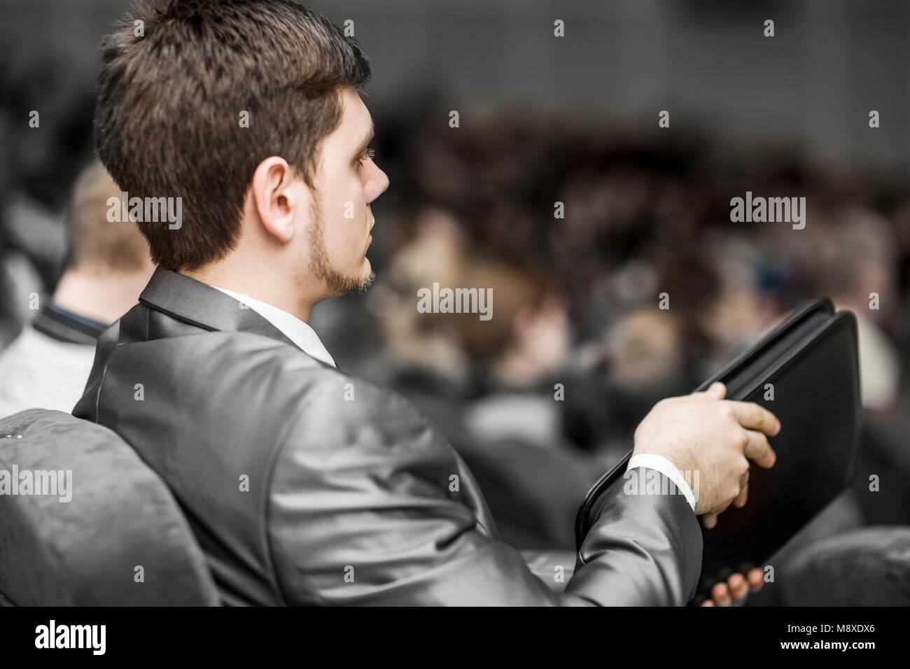 concept of success in business: a successful businessman with a folder for documents, listens to the report sitting - Stock Image