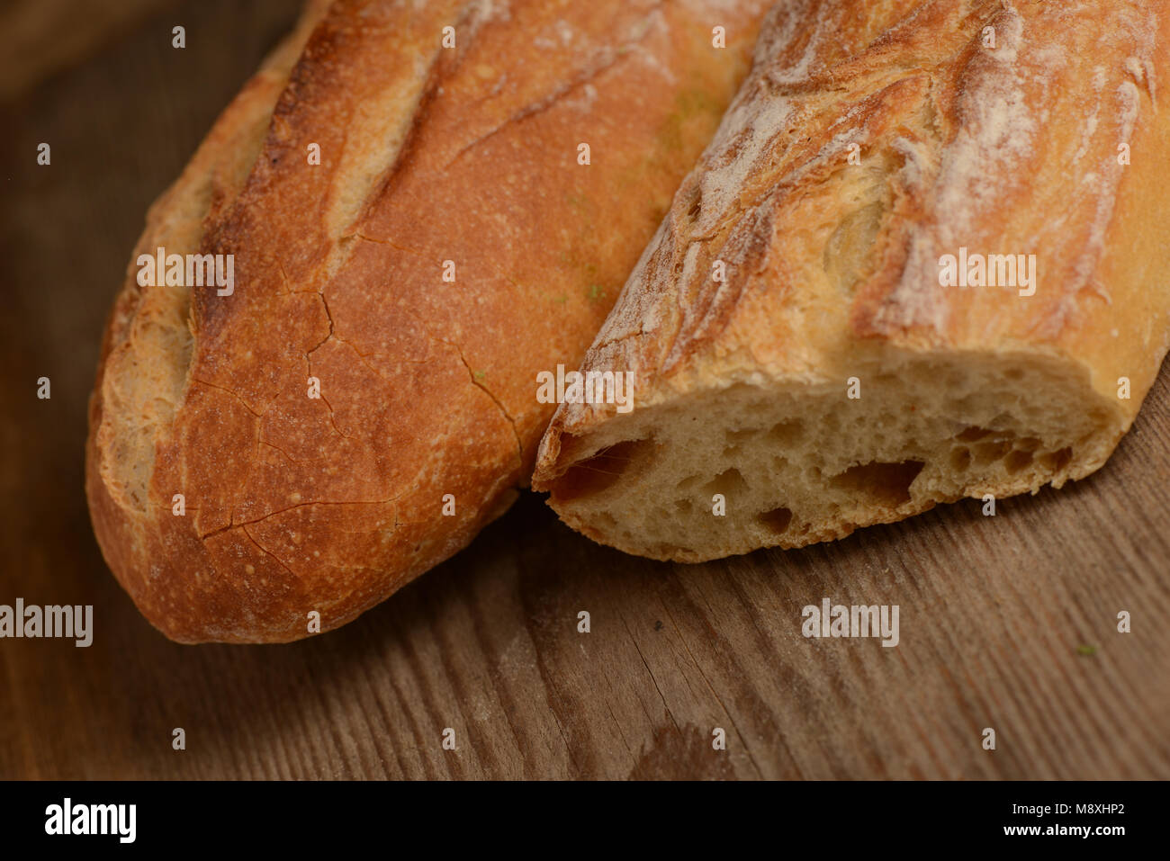 French crusty bread, isolated on a wooden plank - Stock Image