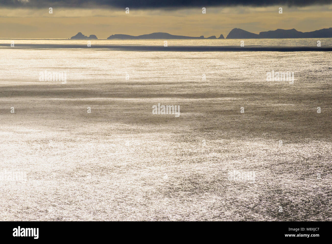 Glittering sea and distant view of the promontory of Ponta de Sao Lourenco, Madeira, from the neighbouring island - Stock Image