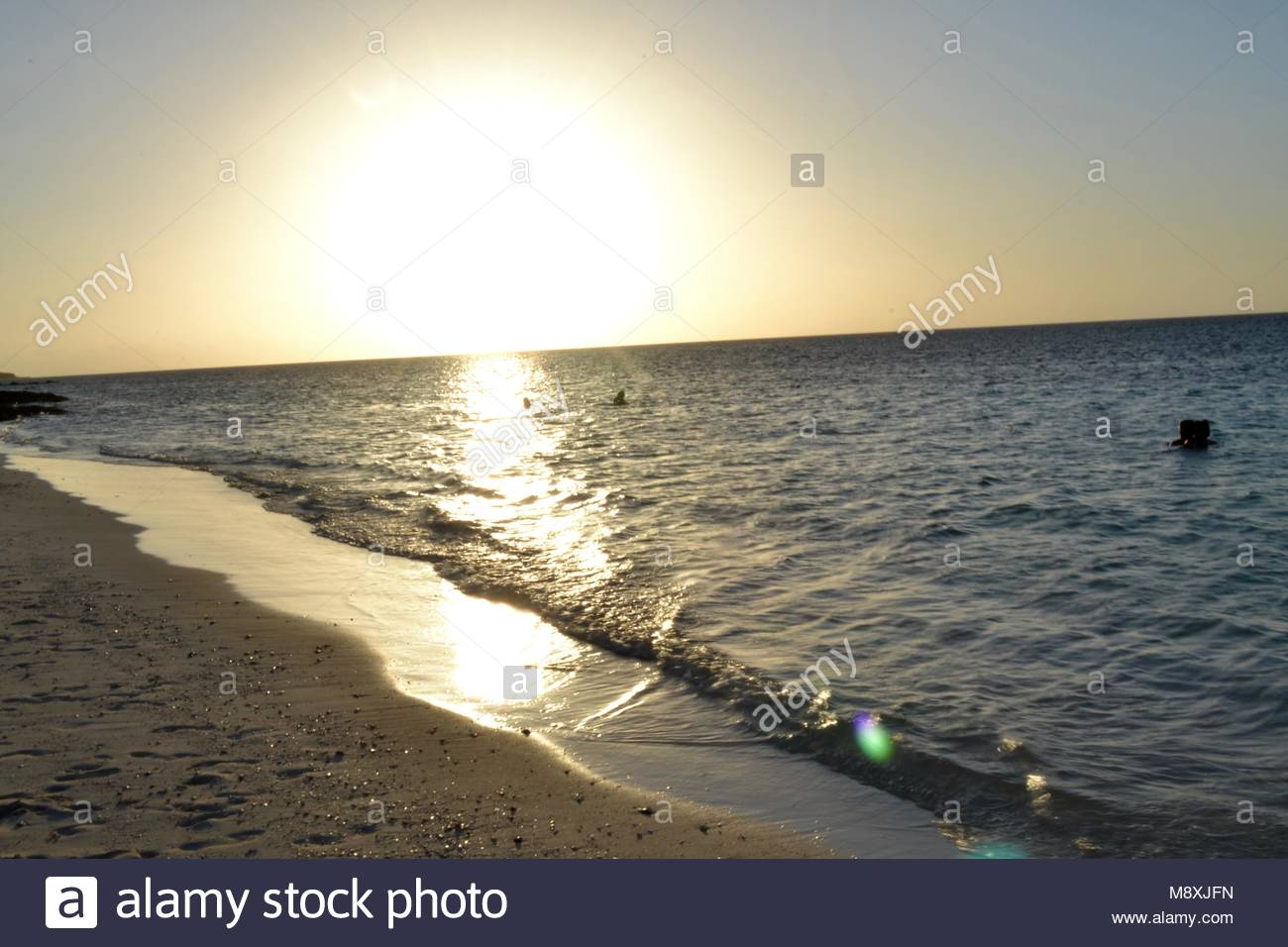 this is a photo of the sun setting over the ocean with waves, sand and out lines of people. - Stock Image