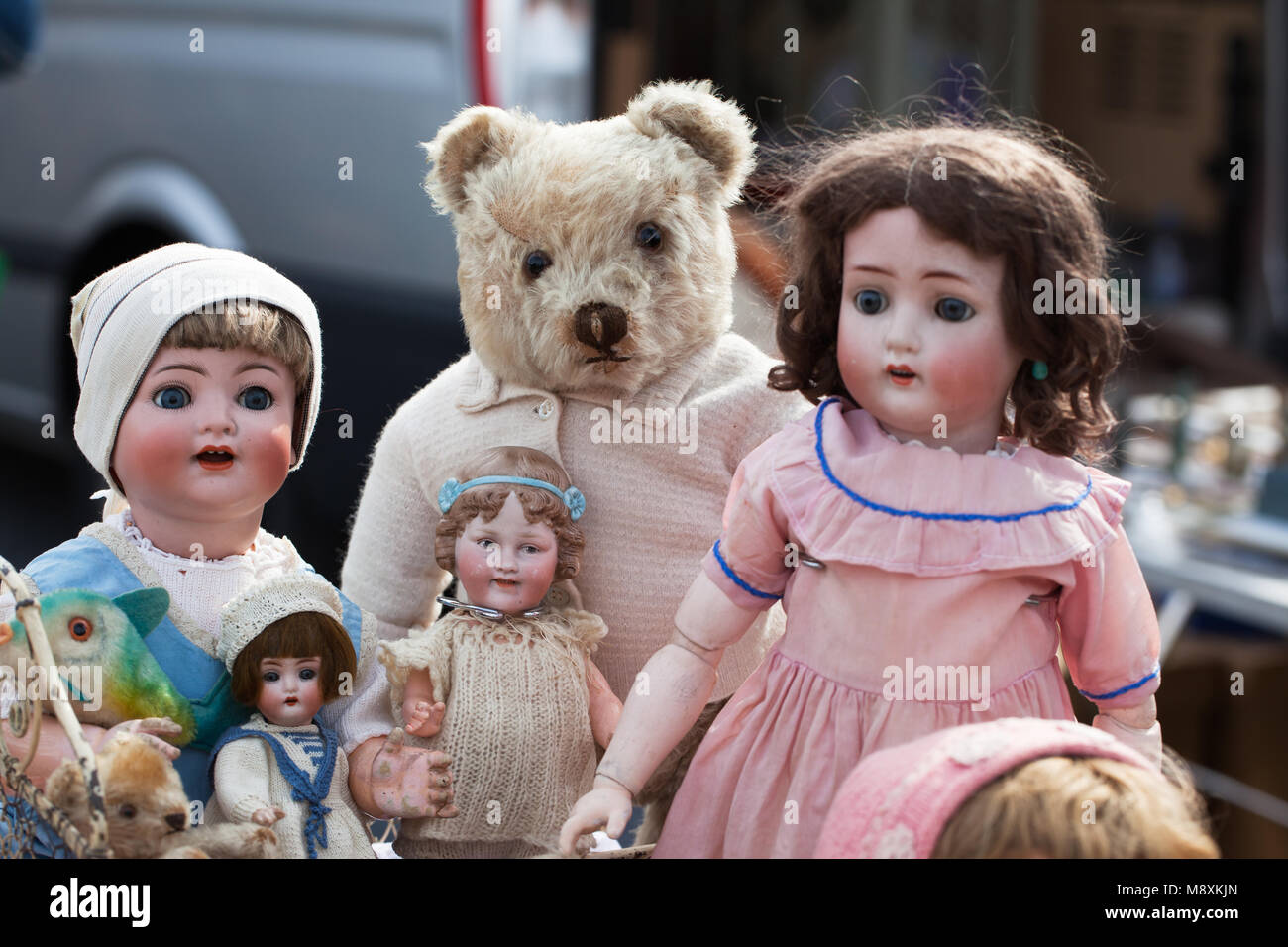 bunch of old dolls with teddy bear at a flea market - Stock Image