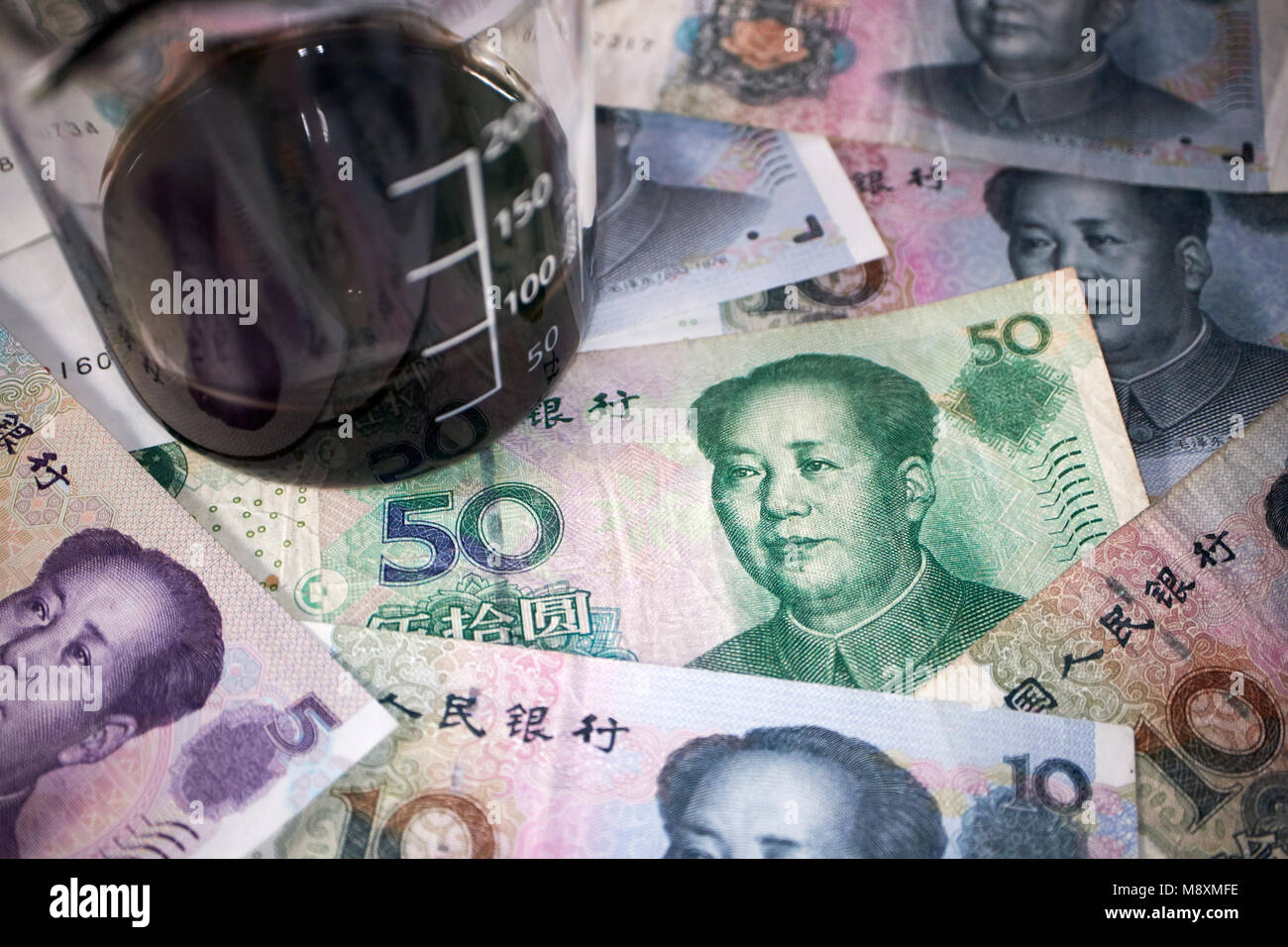 jar of crude oil with chinese yuan renminbi currency trading concept - Stock Image