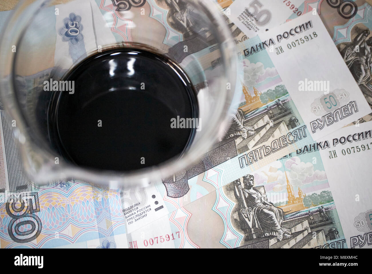 jar of crude oil with russian roubles currency trading concept - Stock Image