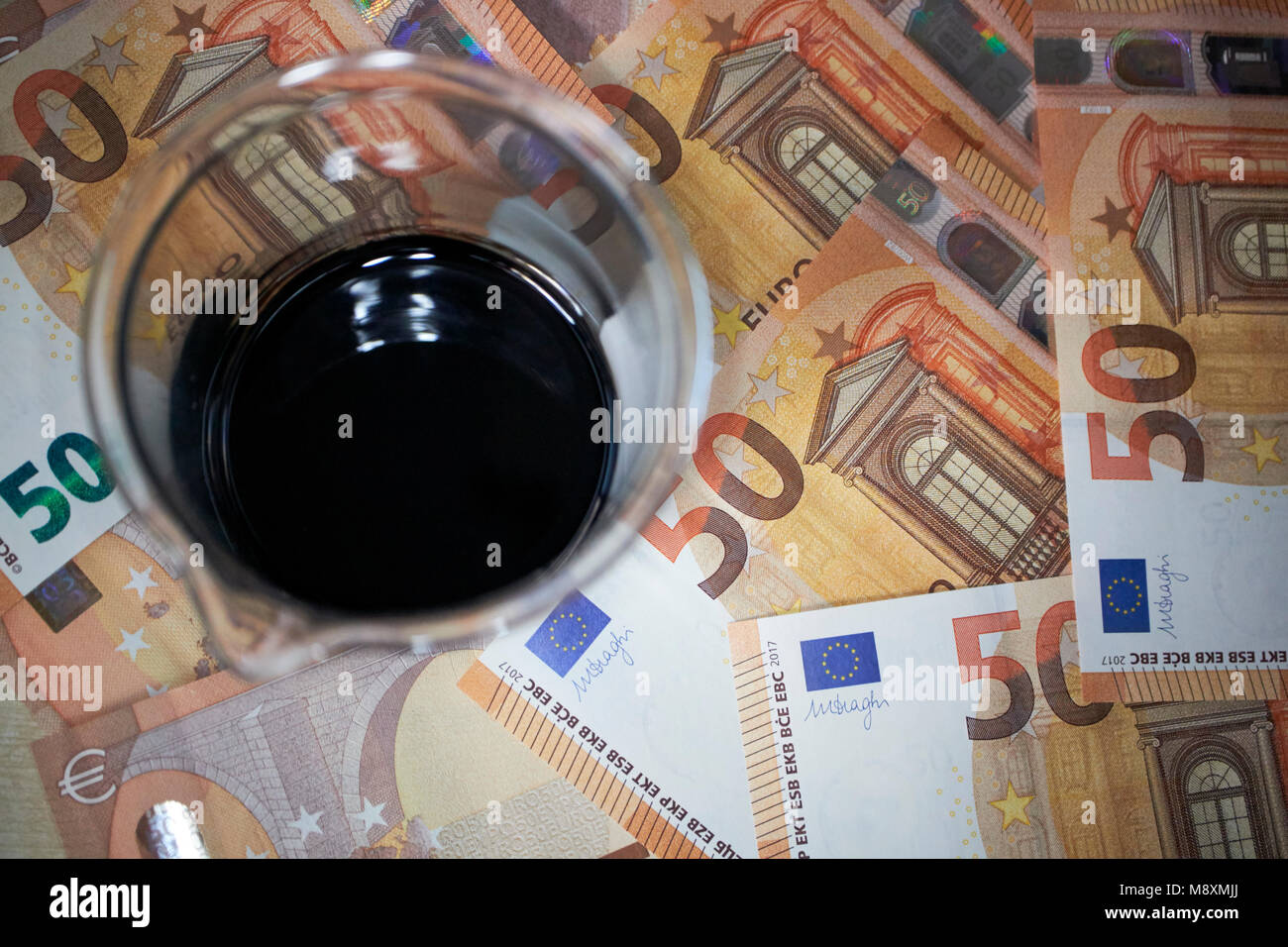 jar of crude oil with currency trading concept - Stock Image
