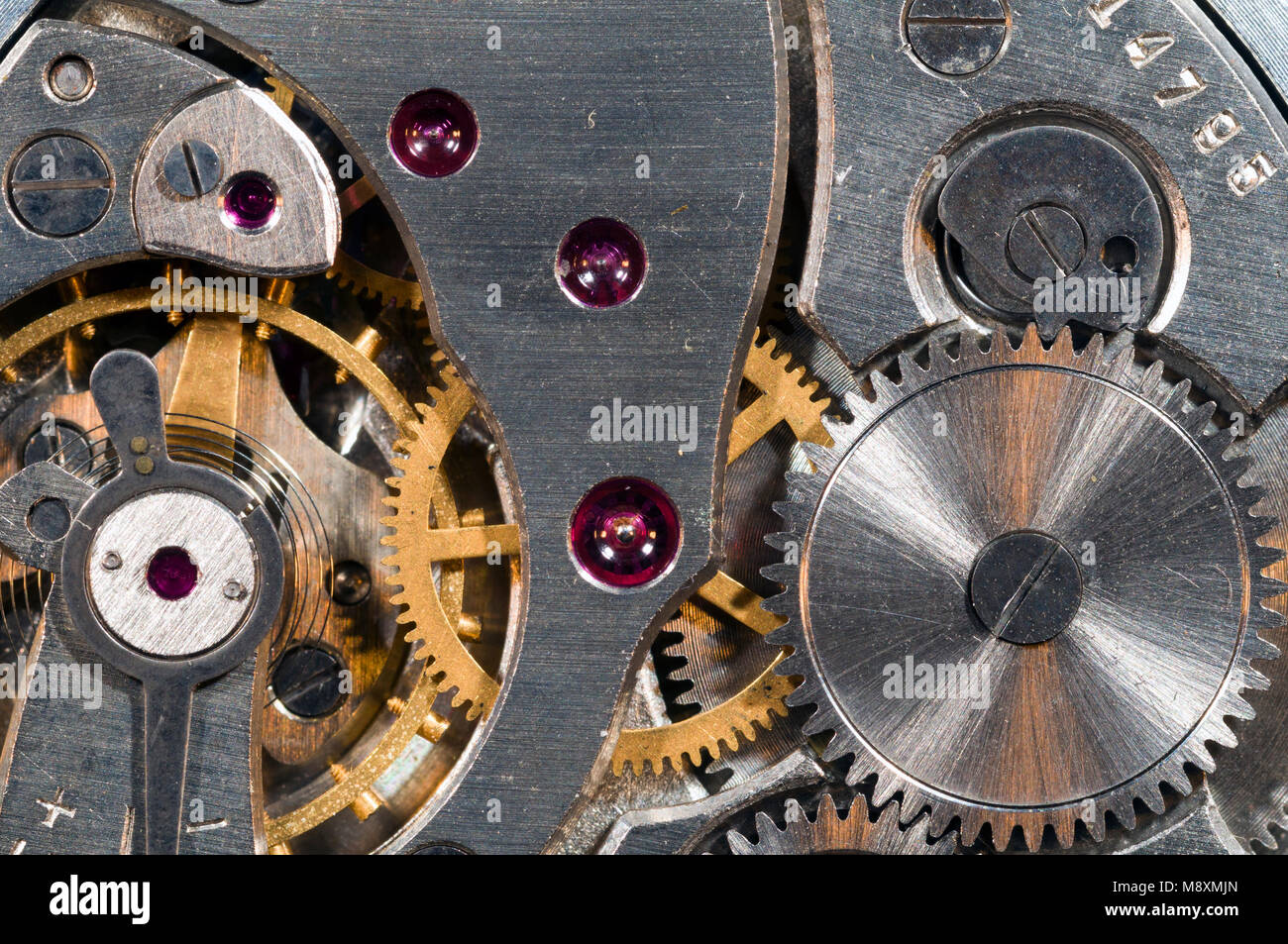 Close-up of the inside of a watch, showing gears, a spring and jewelled bearings. - Stock Image