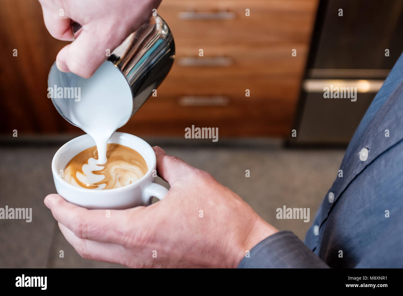 Professional barista pouring steamed milk from stainless steel tumbler into coffee cup making latte art on cappuccino Stock Photo