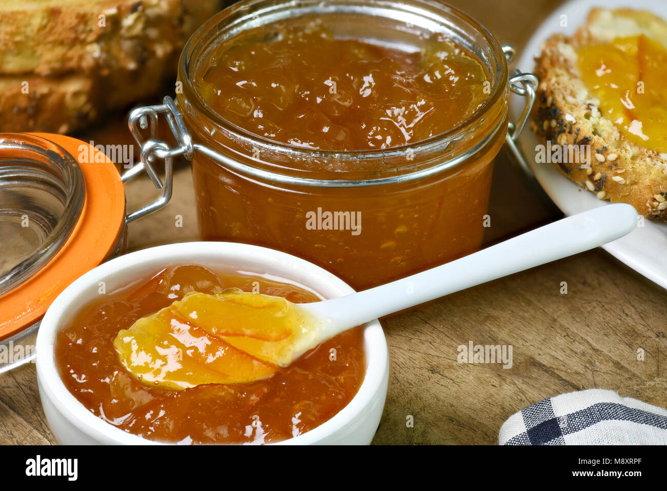 homemade organic marmalade in a small white dish with larger amount in a preserving jar laid out on a old wooden - Stock Image
