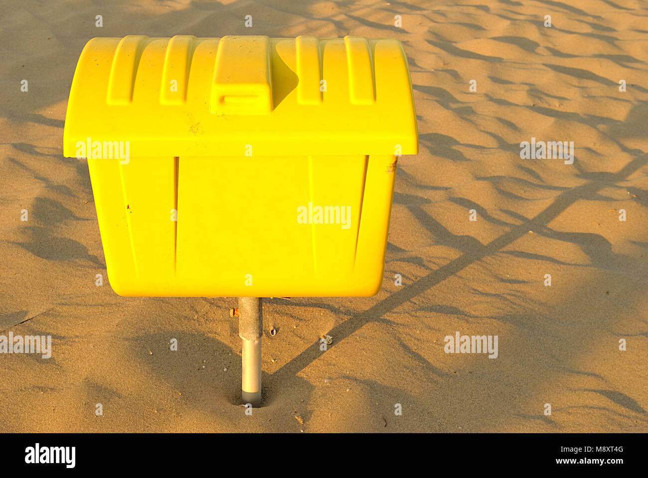 summer sea, yellow trash can on the sand - Stock Image