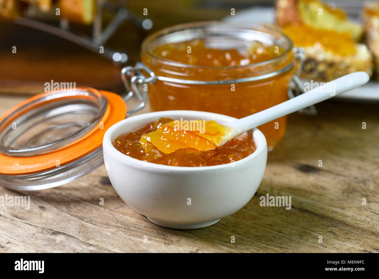 breakfast setting of homemade organic marmalade in a small white dish with larger amount in a preserving jar laid - Stock Image