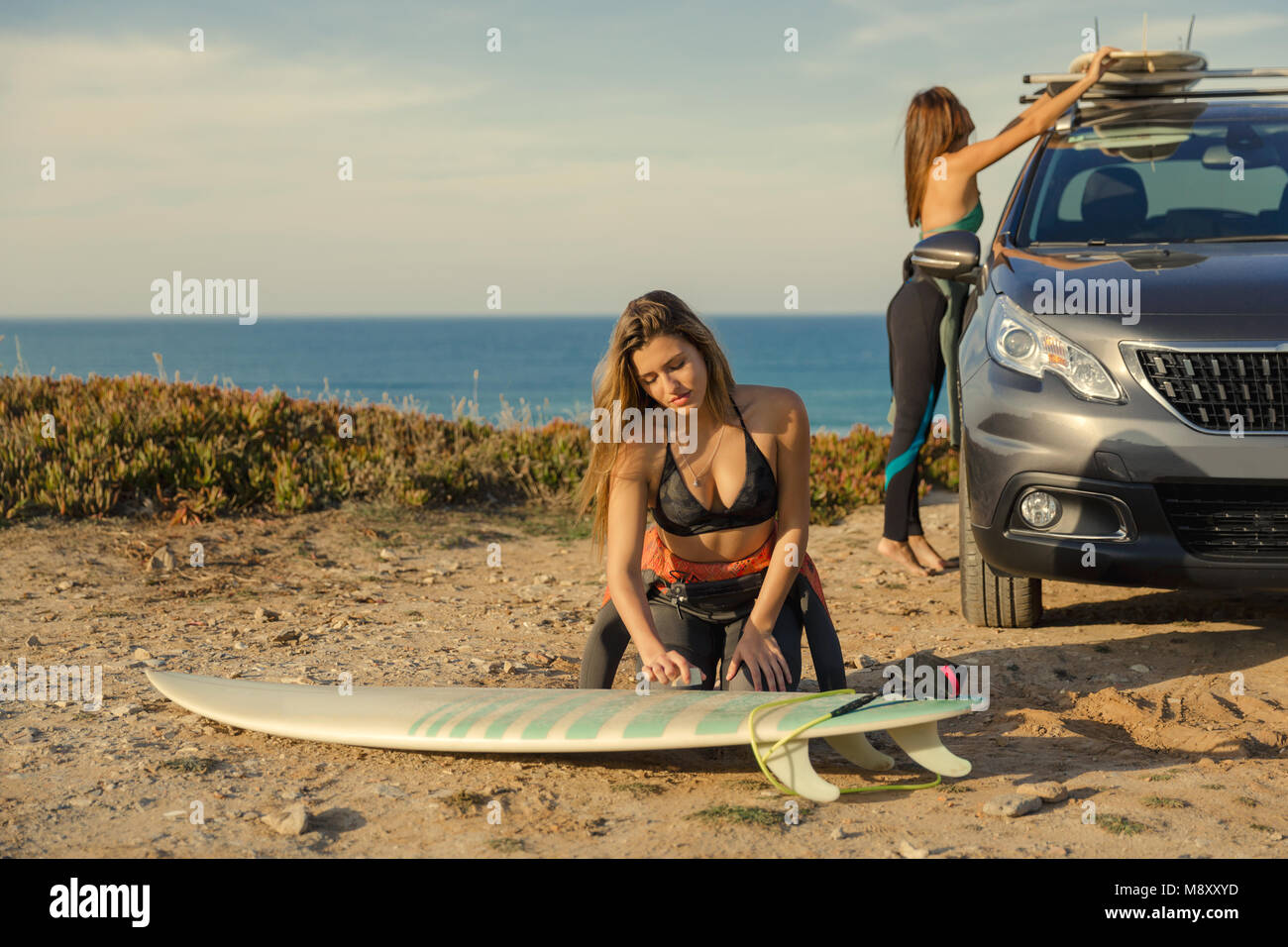 Two beautiful surfer girls near the coastline with her car, and getting ready for surfing - Stock Image