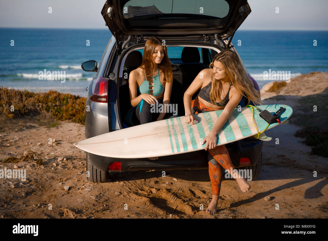 Two beautiful surfer girls sitting on the trunk of car getting ready for surfing - Stock Image