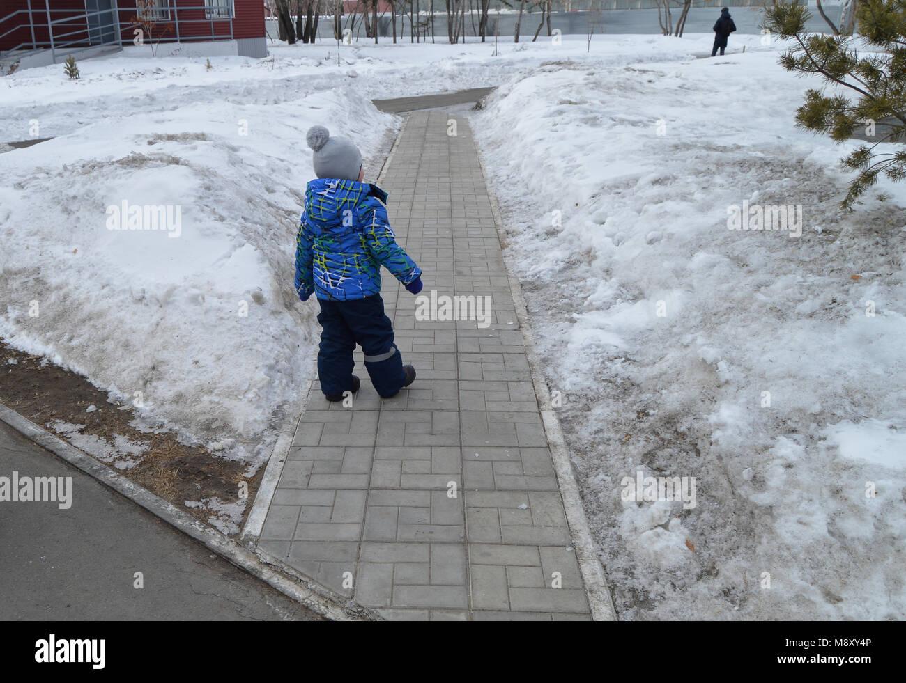 Charming cute little boy in blue jacket walking in winter Park - Stock Image
