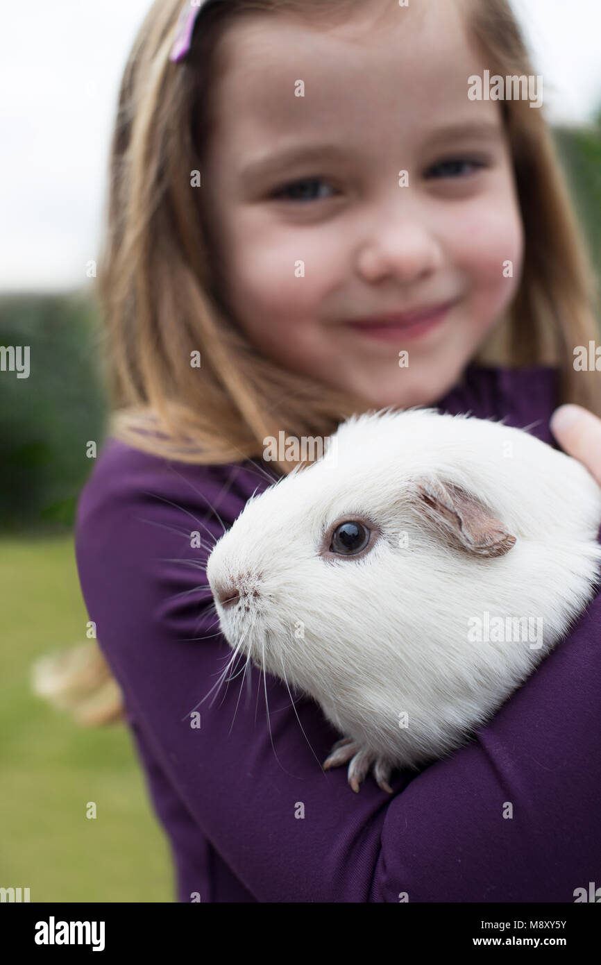 Portrait Of Girl In Garden Looking After Pet Guinea Pig - Stock Image