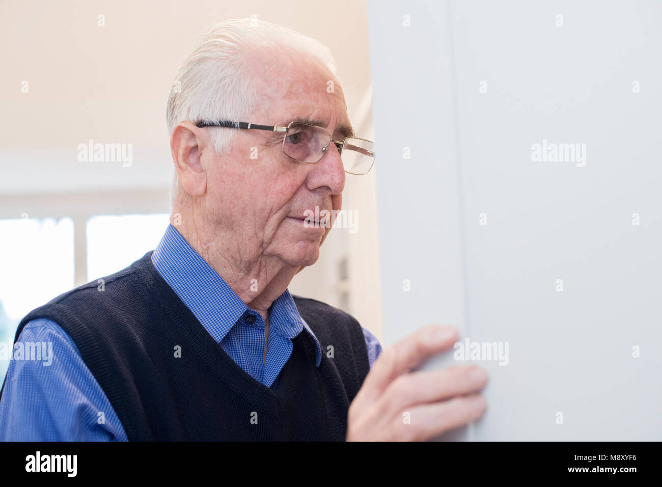 Forgetful Senior Man With Dementia Looking In Cupboard At Home - Stock Image