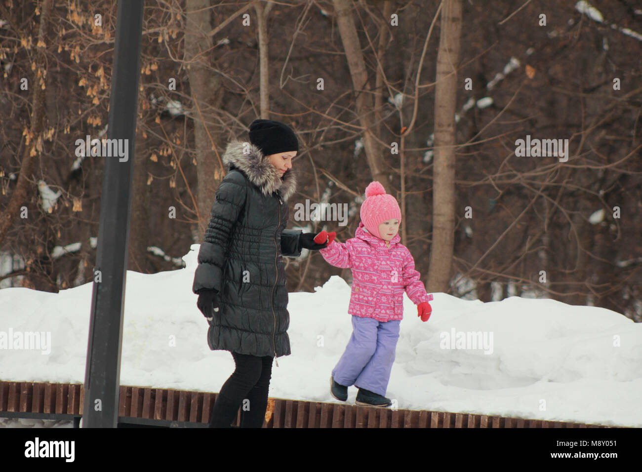 Cute little girl walking with her mother on winter street, daughter breaking out and going independently - Stock Image