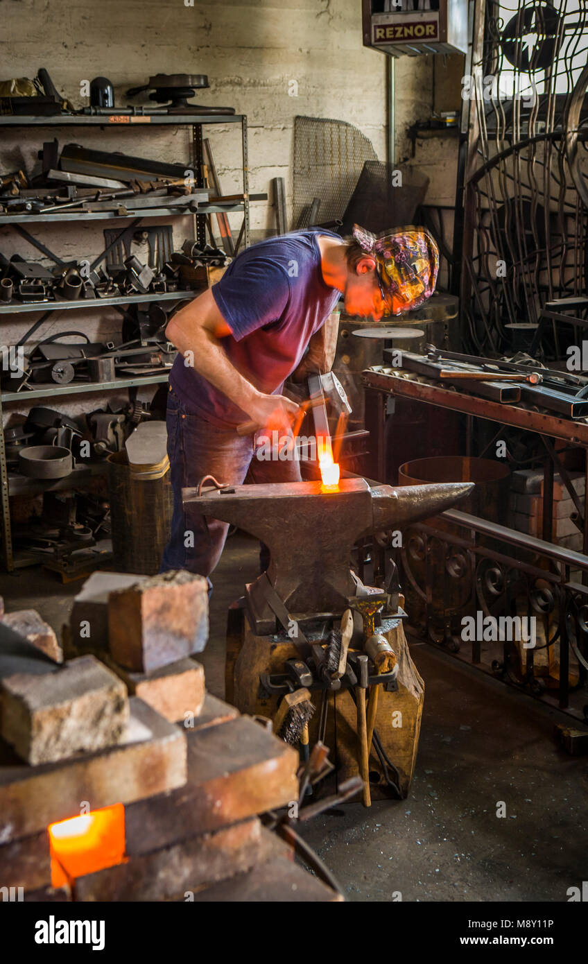 A man working in a blacksmith workshop with hammer and anvil. - Stock Image